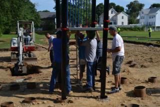 Three people assembling playground equipment at JJ Round Park