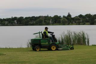 John Deere tractor mowing near the Lake