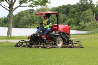 Toro tractor mowing near the Lake