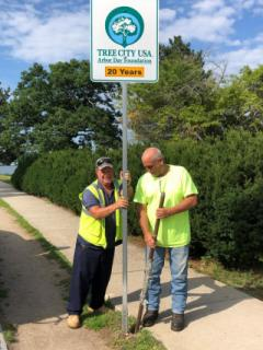 Two men installing Tree City USA sign